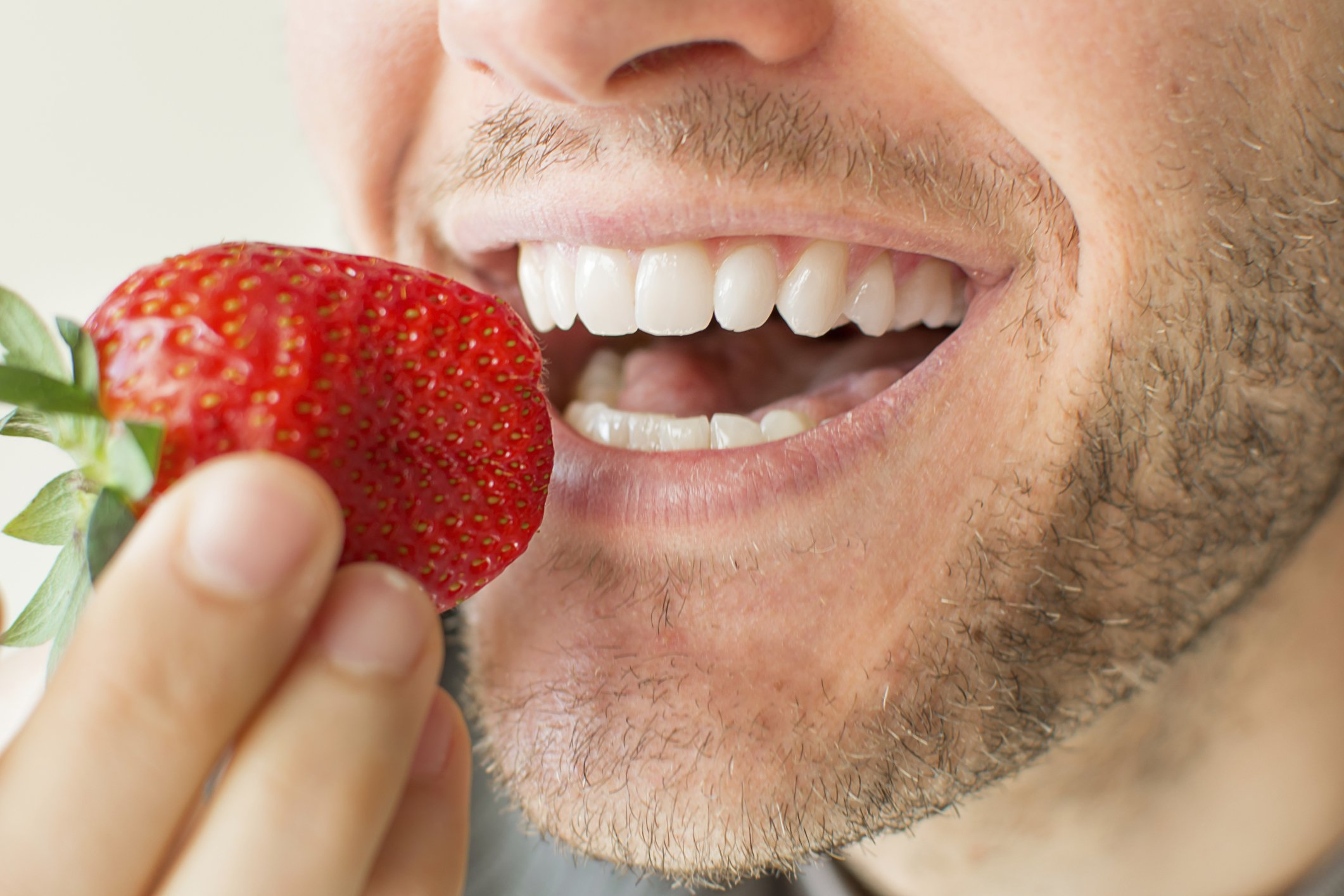 Closeup of a man's face eating strawberry